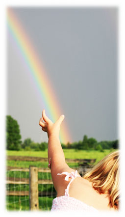 Small Child reaches to grab a Rainbow